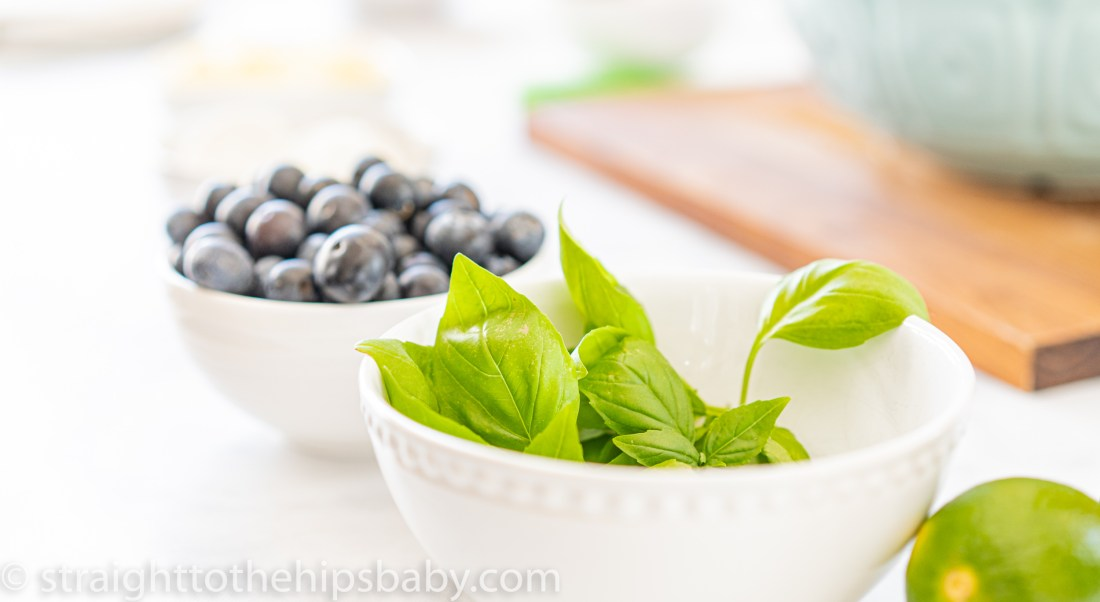 white bowls of blueberries and fresh basil