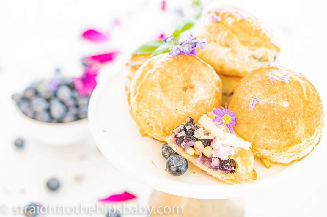 beautifully golden puff pastry bites with blueberries, corn, and goat cheese