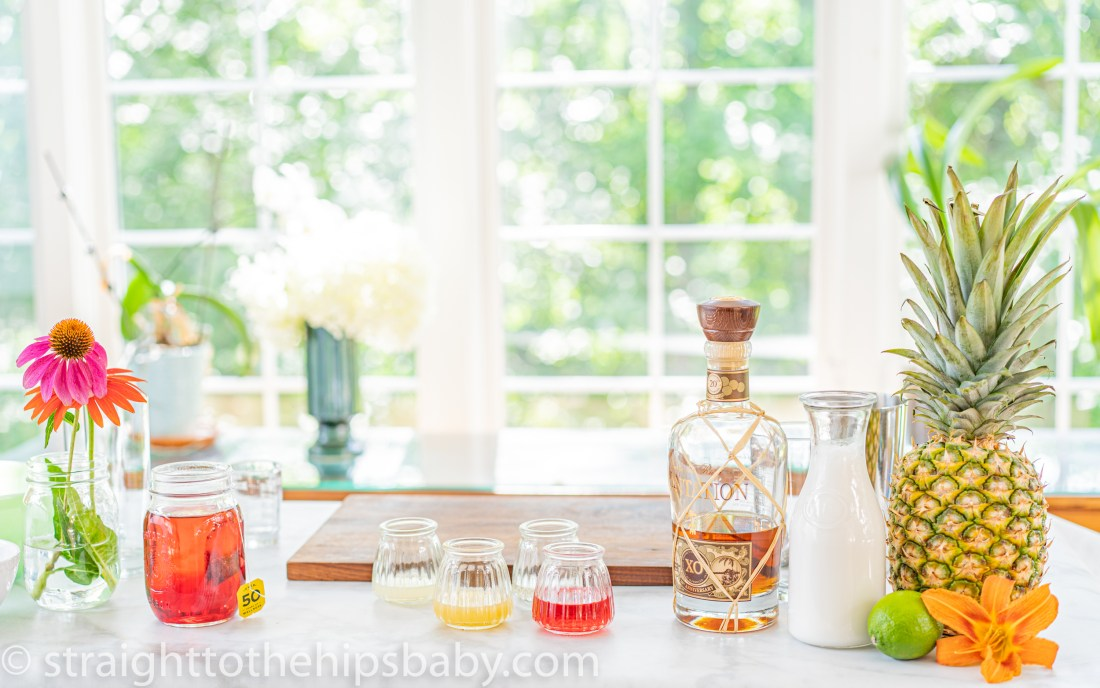 a display of all the ingredients for a pineapple & hibiscus daiquiri on a bright summer day