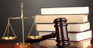 Wooden gavel, golden scales of justice and books