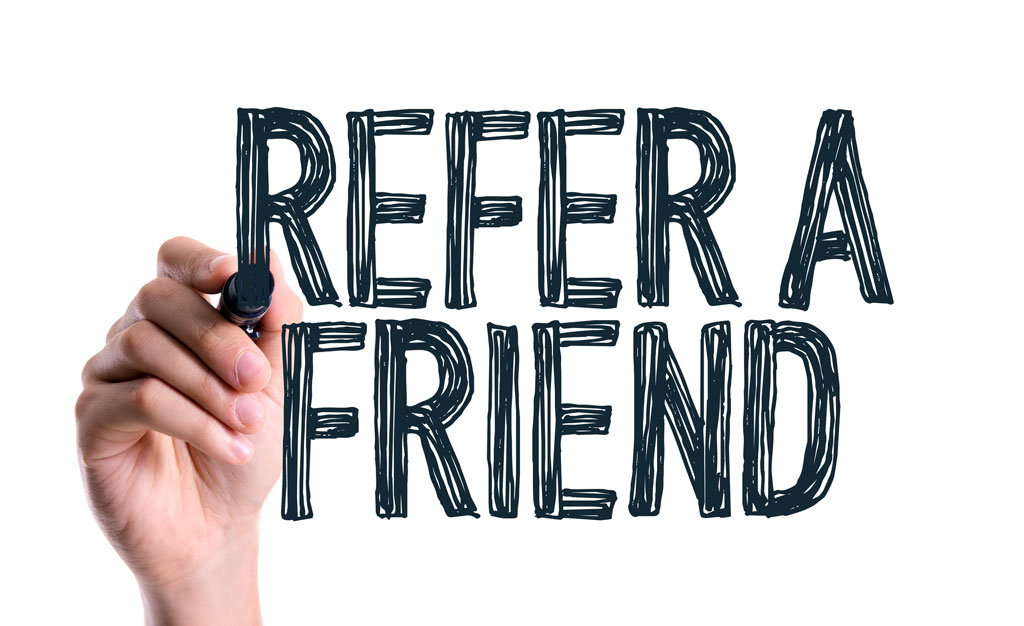 Hand with marker writing the word Refer a Friend