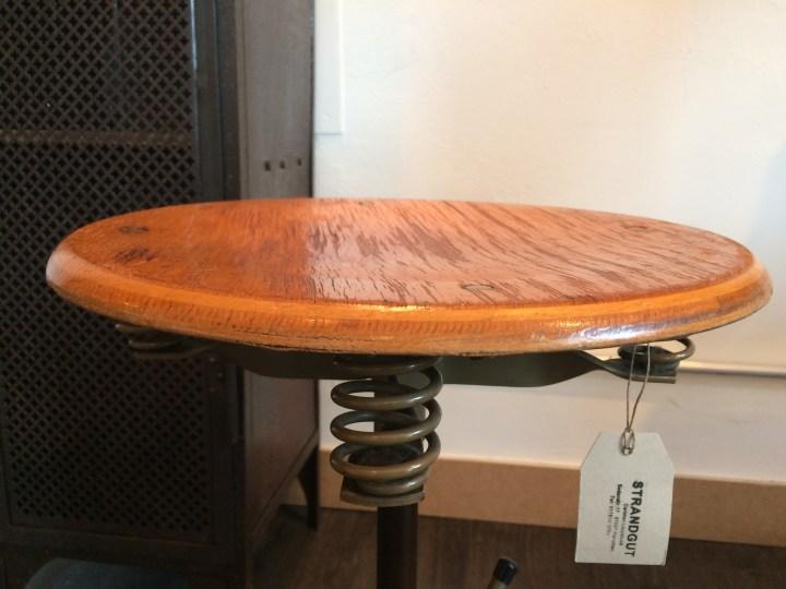 Dreh und höhenverstellbarer Arbeitshocker mit Sitzfedern unter der Sitzplatte holz