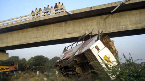 Indian police officers look down from a bridge at the wreckage of a bus after an accident in Sawai Madhopur district, nearly 185 kilometres west of Jaipur, India, Monday, March 15, 2010. (AP / Rajasthan Patrika)