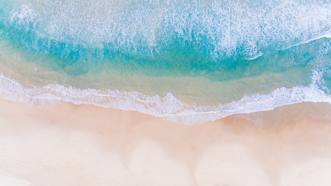 A stock image of where the tide meets a sandy beach.