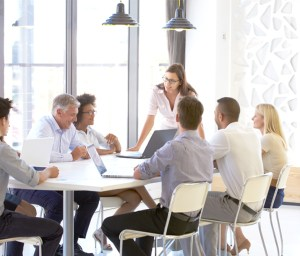 Group meeting around table with executive coach. If you're looking to improve your work, try coaching for success.