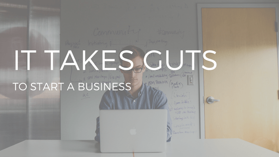 "THE TEXT ""IT TAKES GUTS TO START A BUSINESS"" OVER PHOTO OF MAN IN MID-20S TYPING ON SILVER LAPTOP IN FRONT OF A WHITEBOARD WITH WRITING ON IT"