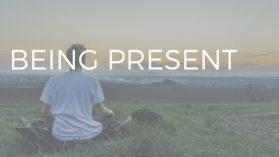 "the text ""being present"" over a photo of a man meditating"