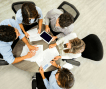 a group of people working around a round table, shot from above
