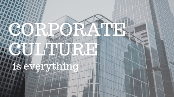 """Glass office towers with white text reading """"corporate culture is everything"""" on top"""