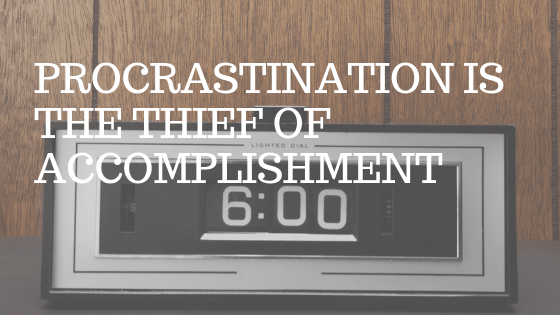 """an old-timey clock radio in a wood paneled room. White text over picture reading """"procrastination is the thief of accomplishment"""""""