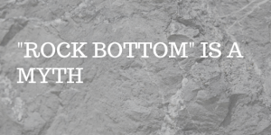 "GREY ROCK SURFACE WITH TEXT ""ROCK BOTTOM IS A MYTH"""