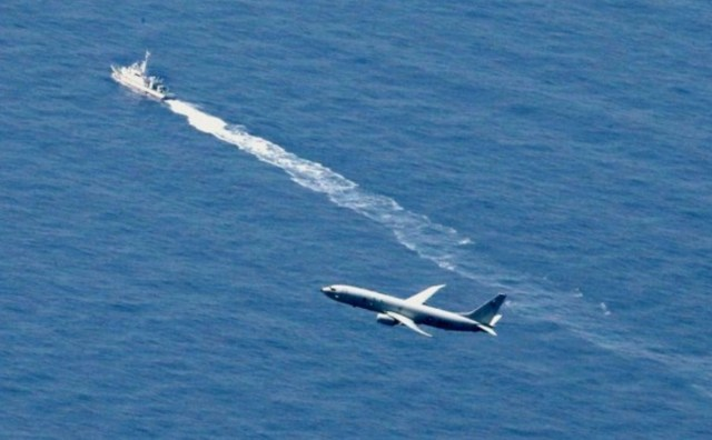 P8 Poseidon flying over a Japanese navy vessel