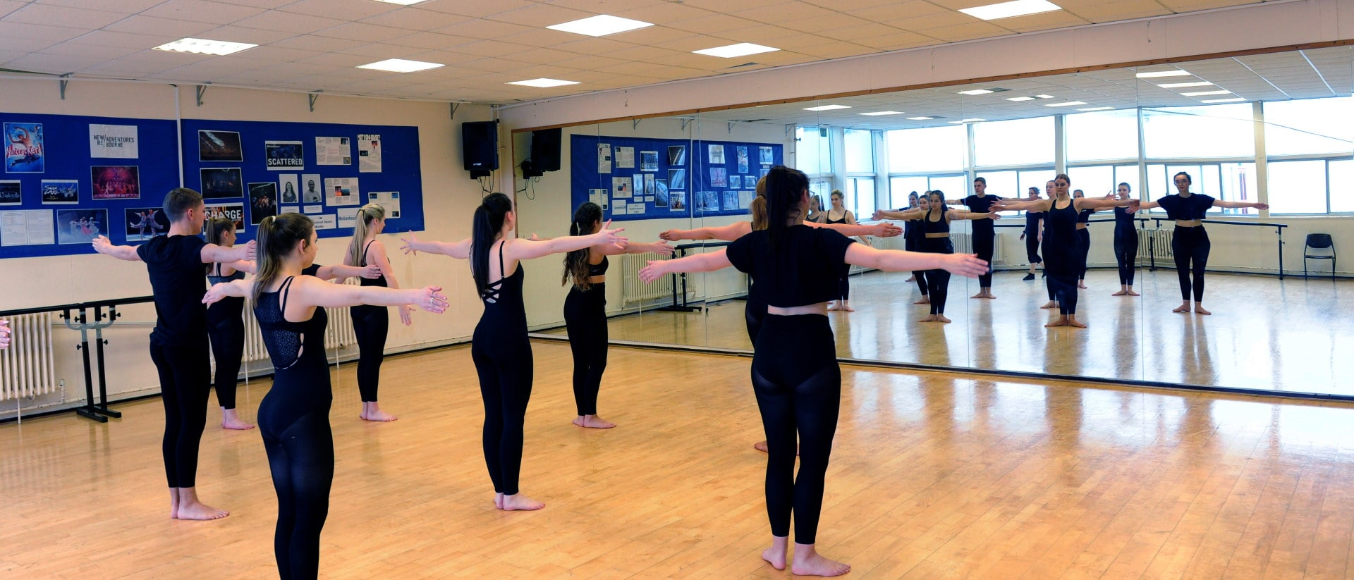 Students in dance studio practice in front of a wall-to-wall mirror.
