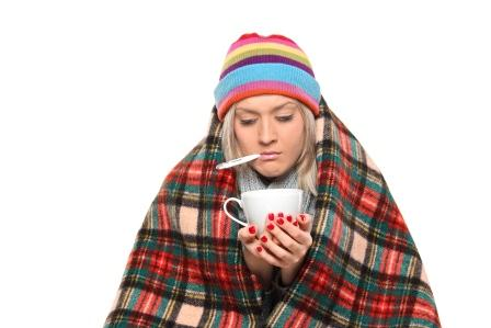 Ill woman covered with blanket holding a tea cup