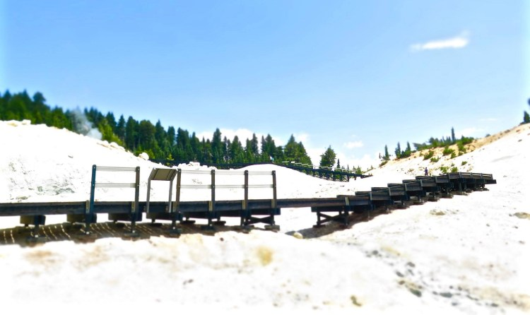 A process called hydrothermal alteration which happens when acidic water chemically changes minerals in rocks produces a white material rich in kaolinite clay and silica which is abundant at Bumpass Hell.