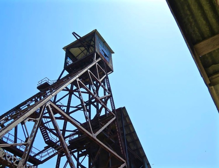 The head frame is 135 feet tall, and composed of iron beams. The original 100 foot tall wooden headframe burned (along with most of the surface developments) in 1928. Debris from the burning headframe fell down the main shaft, blocking any chance of exit for the miners still working thousands of feet below. In the aftermath of the Argonaut Mine disaster, a connecting tunnel was left in place at the 4,600 foot depth between the two mines. This tunnel allowed the miners to escape unharmed.
