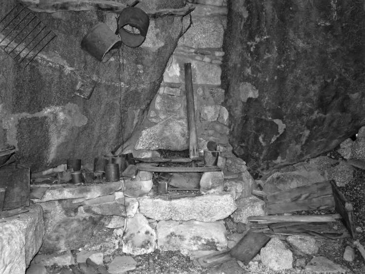 A masonry and iron stove is built into the northern end of the cabin...