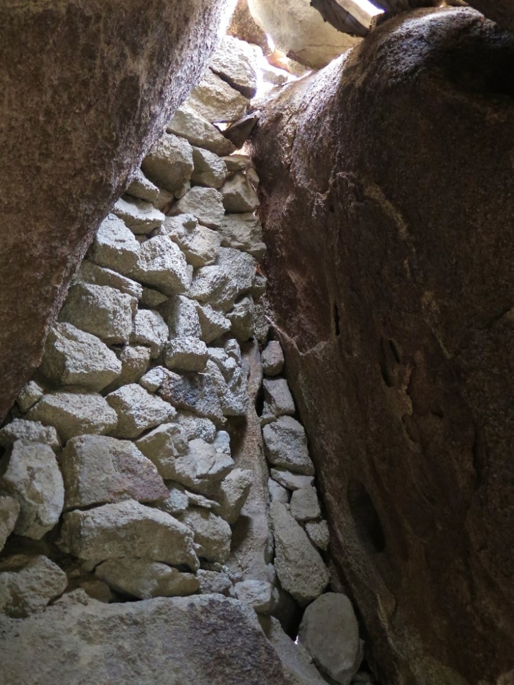 Rocks and cement create walls and seal up several openings between the boulders.