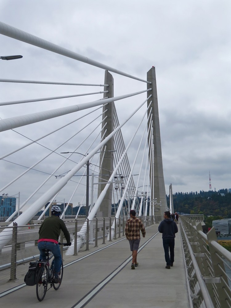 The 780-foot-long main span deck is separated into a 31-foot-wide transitway between the tower legs to accommodate two lanes of track and two flanking multi-use paths for pedestrians and cyclists. — with Darby Aldaco.