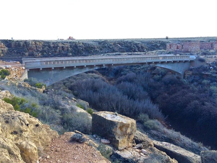 In 1914 Arizona State Engineer Lamar Cobb selected and surveyed the site for a bridge over the canyon and purchased plans and specifications for a long-span concrete arch from the Topeka Bridge & Iron Company of Kansas for $500.