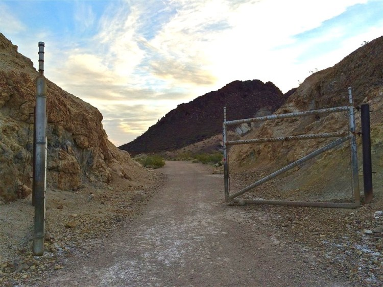 The flat area before the gate is the approximate site of Lawler, the railroad junction where the Six Companies Railroad (built to haul aggregate for the concrete used in the dam, power houses, and ancillary works) met the U.S. Government railroad that ran from Boulder City to the edge of the canyon above the dam. The Lawler junction probably consisted of a short section of double track, three turnouts, and a shed for switch tenders and a telegraph operator.