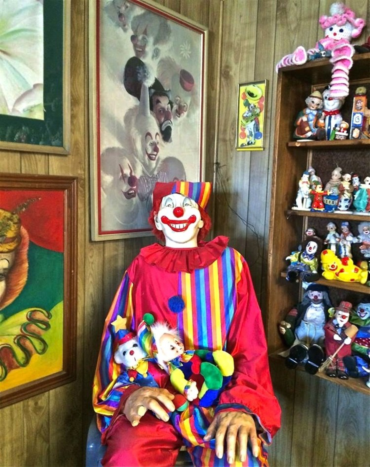 On each of the walls are hung portraits of famous clowns, from Bozo to Pagliacci, their soulless eyes intent on watching your every move from their faux-gold frames.