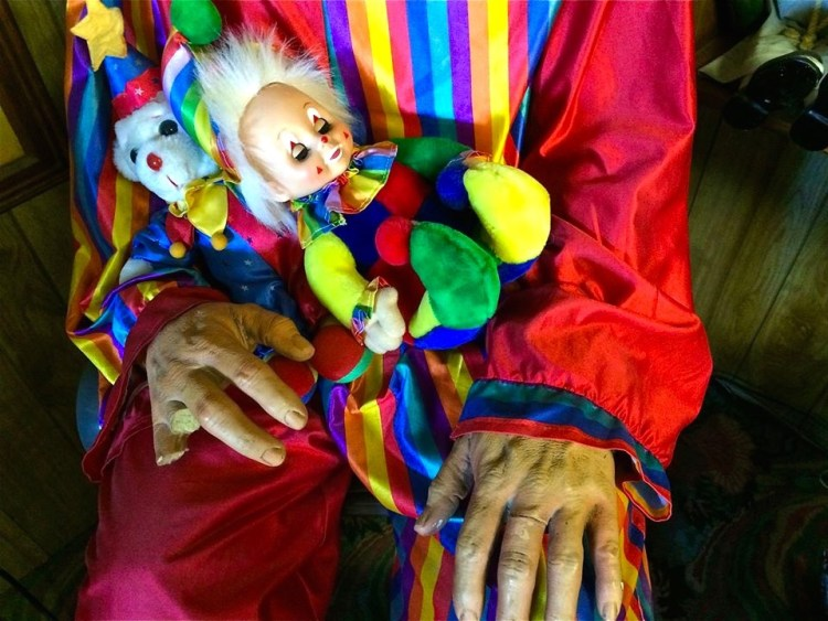 From the moment travelers enter the adjoining offices they are greeted by a life-size clown figure sitting in a chair, with life-like hands and missing fingers.