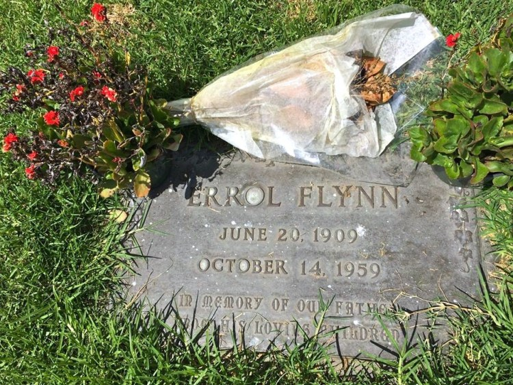 Errol Flynn (1909-1959) lies in a very humble grave in an outside garden with dead flowers:(