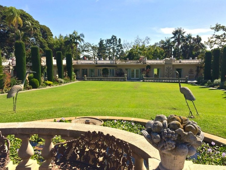 The Formal Mall Garden is a perfectly-manicured stretch of emerald lawn flanked by cypress trees, perennial flower borders, rare specimen Cycad 'palms' and is bookended by the blue tiled pool at one end, and the Robinson home at the other.