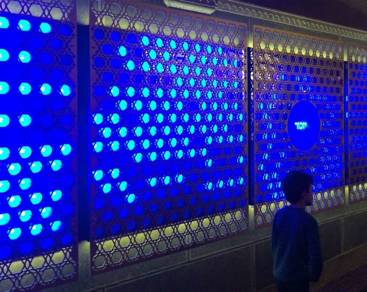 "The two-part wall consists of 10 electronic panels filled with a total of 1,700 azure-blue spheres, each one intended to memorialize a member of the congregation. With the help of artists Aaron Bocanegra, Mattia Casalegno and Bill Kronholm, the panels will be programmed to light each sphere during the week that person died, as part of the Jewish ritual of remembering the deceased on the anniversary of his death. For one week each year, all the spheres will be lit. In the center of one of the panels is a large round plate bearing the Hebrew word yizkor, meaning ""remember."""