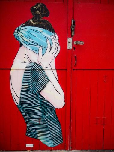 Jana und Js Mural zeigt eine Frau mit verbundenen Augen vor einer roten Wand