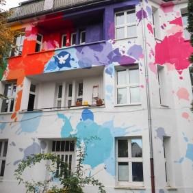 unbekannte Künstler haben bunte Farbklekse und eine Friedenstaube auf die Hauswand gemalt