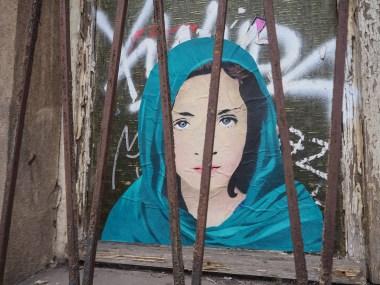 Oni klebte das Paste up einer jungen Frau mit Kopftuch hinter ein Fenstergitter