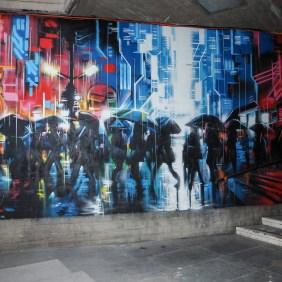 Mural von Dank dass Menschen im Regen in einer Stadt darstellt