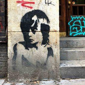 ein zur Seite schauender Junge wurde als Stencil neben einen Hauseingang gesprüht