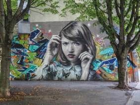 Portrai eines Mädchens von Mantra und Takt an einer Wand im Park