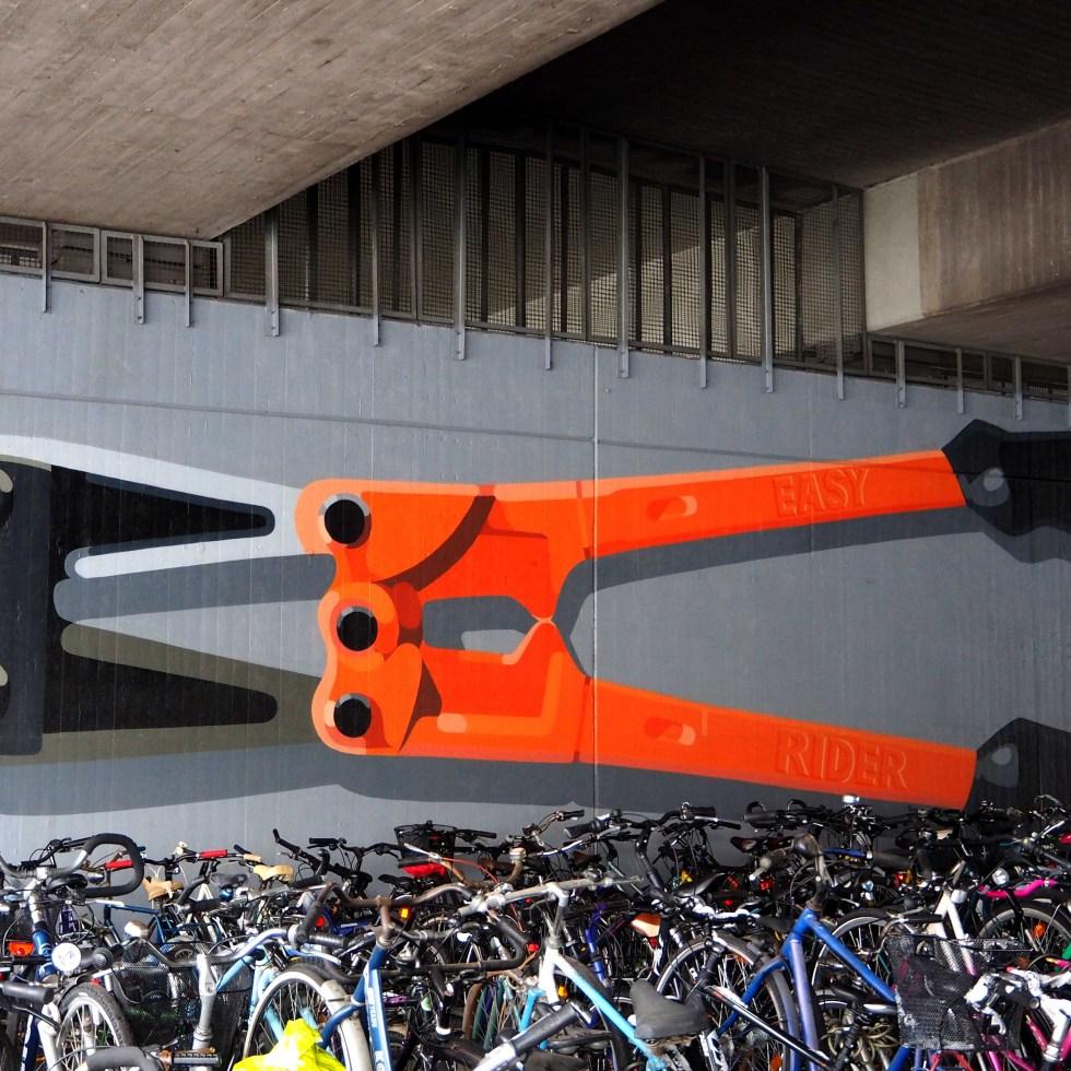 unter einer Brücke, ein Mural dass vor sehr vielen Fahrrädern einen Bolzenschneider zeigt