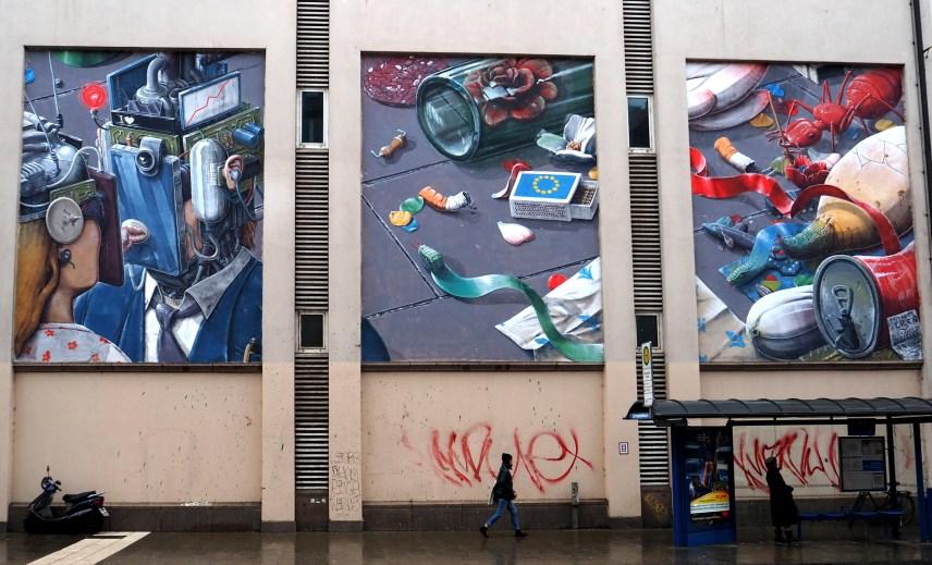 vor einer Bushaltestelle finden sich drei große Murals die die Dekadenz der Gesellschaft darstellen soll