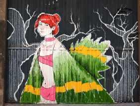 eine rothaarige Frau trägt einen grünen Poncho