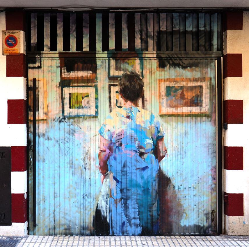 eine Frau in Kittelschürze steht vor Bildern, vielleicht in einem Museum