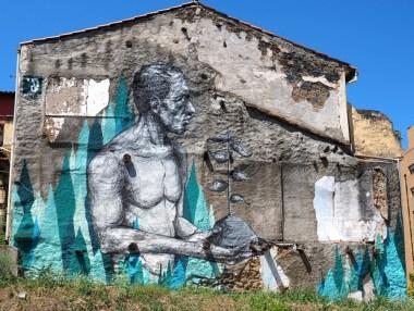 Mural mit einem Mann, der ein Pflanze in den Händen hält