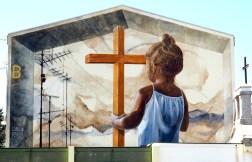 ein Mädchen hält ein Holzkreuz
