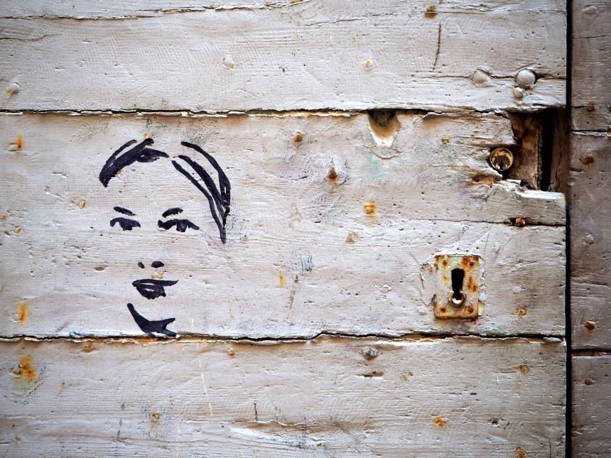 Frauenzeichnung auf getünchter Tür