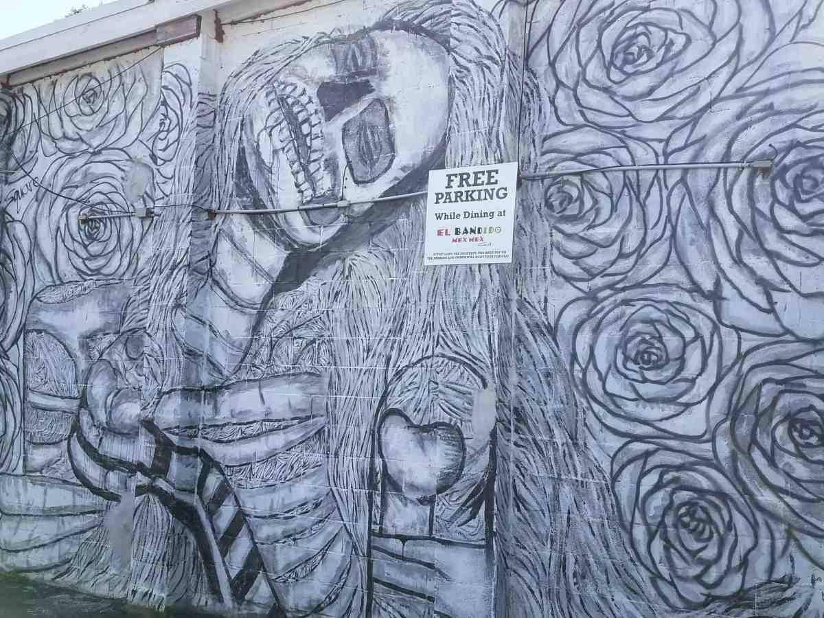 Mural featuring a skull and flowers by artist 2 Square in Little Five Points
