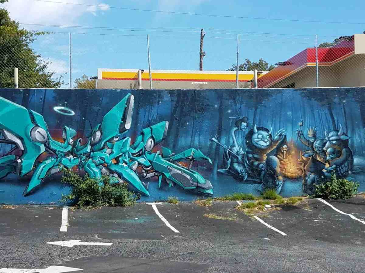 Graffiti featuring creatures around a fire by artist Mr. Totem in Little Five Poiints