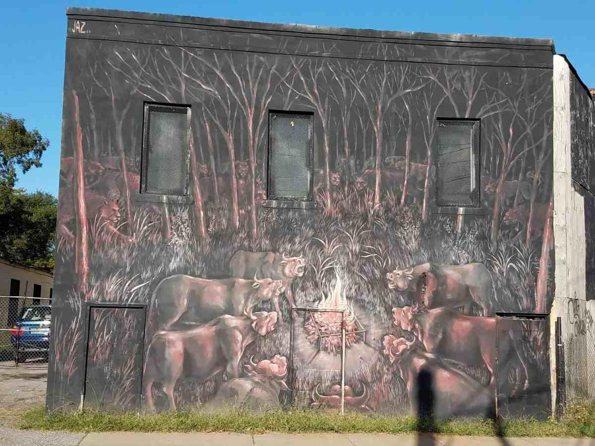 Mural of cows around a fire by artist Jaz