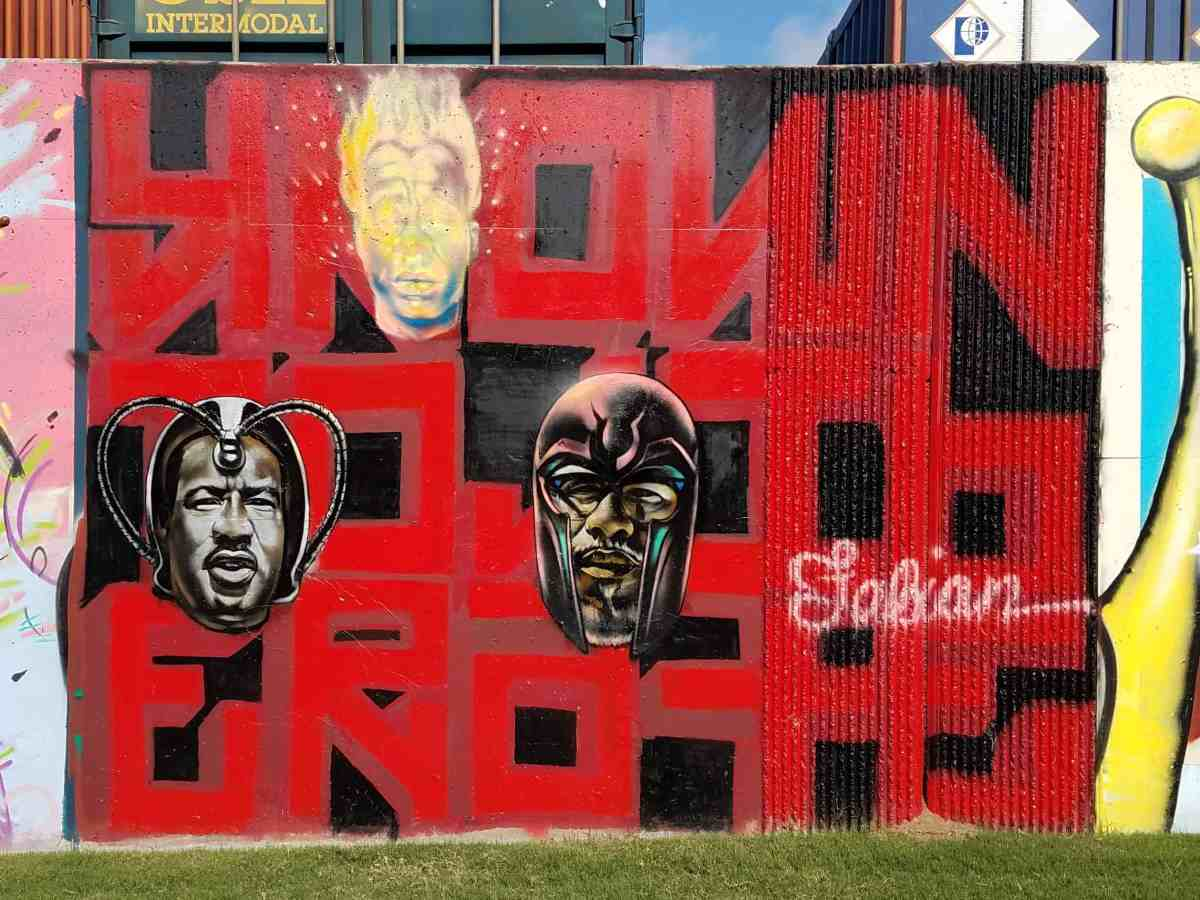 Mural of three faces over lettering