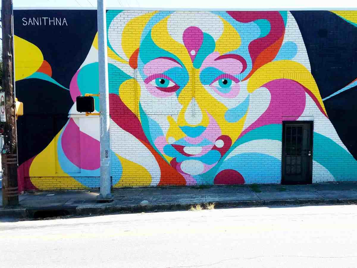 Street art featuring a multi-color woman's face by Sanithna