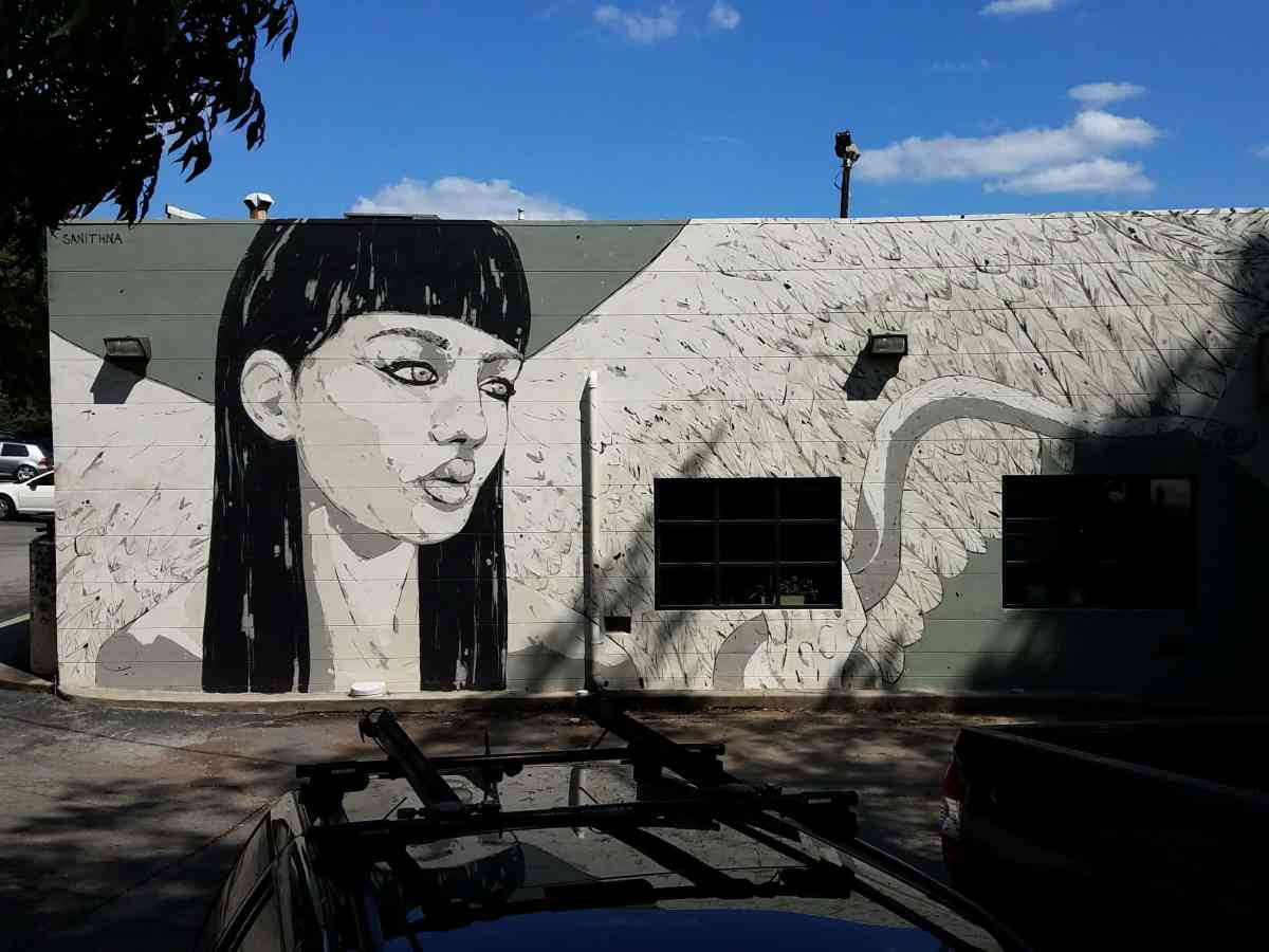 Mural of a woman in grey by artist Sanithna
