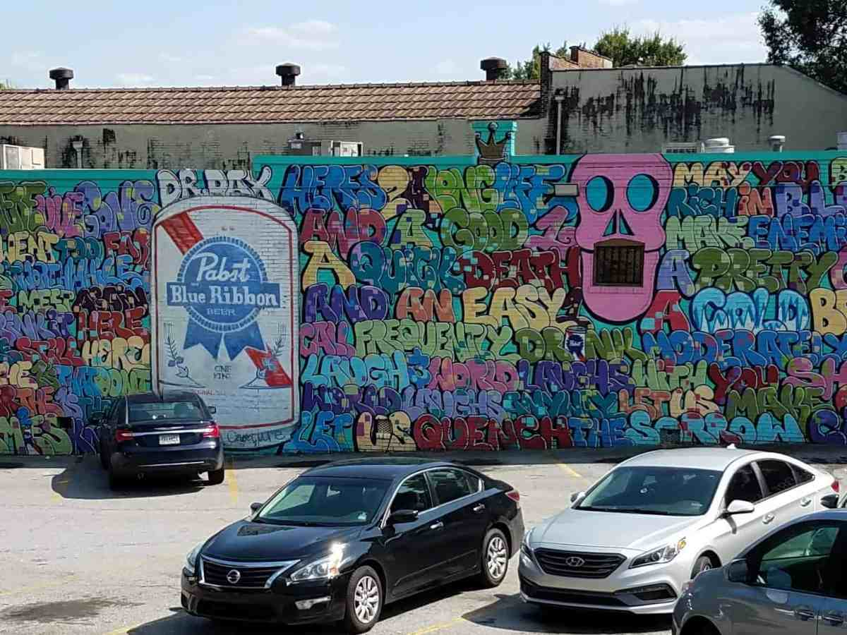Mural featuring baloon letters and a beer can by artist Dr. Dax